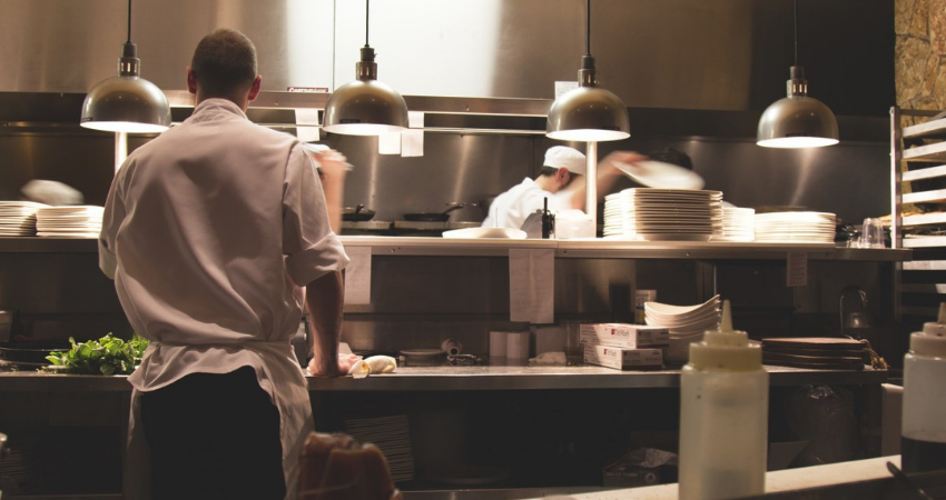 Chefs in a kitchen with an restaurant grease trap