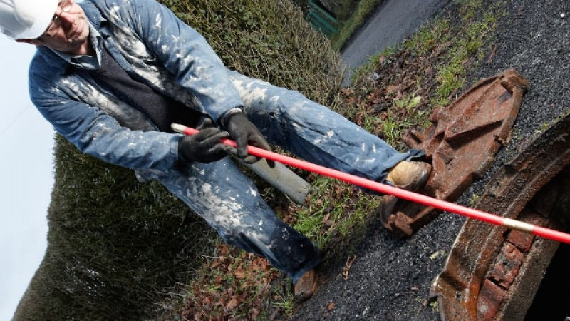 Plumber using drain rods to clear an external drain