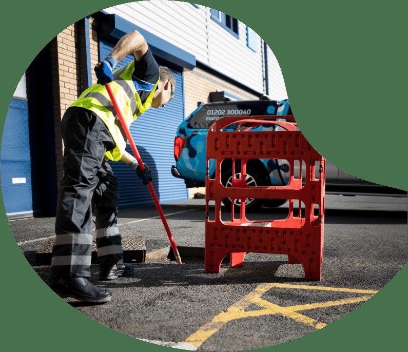 Maintain Drains plumber using drain rods to unblock an external drain