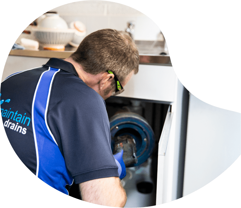 Maintain drains plumber unblocking an internal drain in a kitchen
