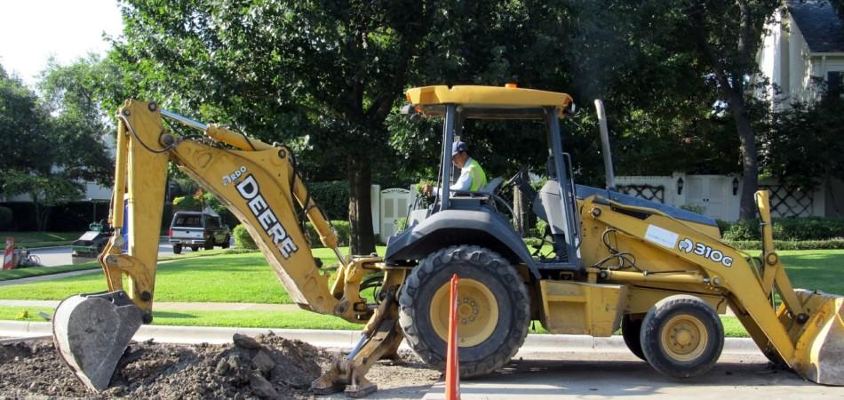 Digger excavating drain pipes