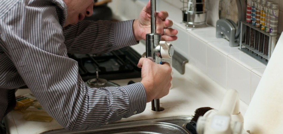 Plumber repairing a blocked sink in kitchen
